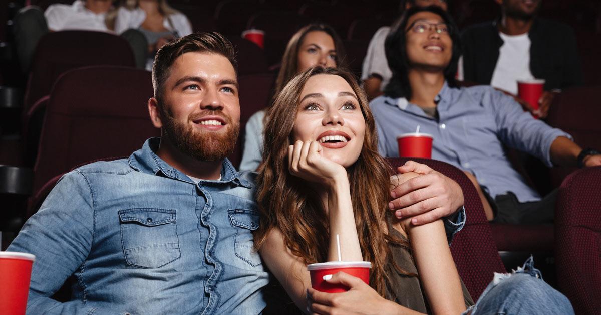 Glückliches Pärchen im Kino mit Popcorn